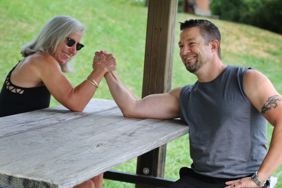 Robynn Shannon and Lou Slimak arm wrestle on a picnic table